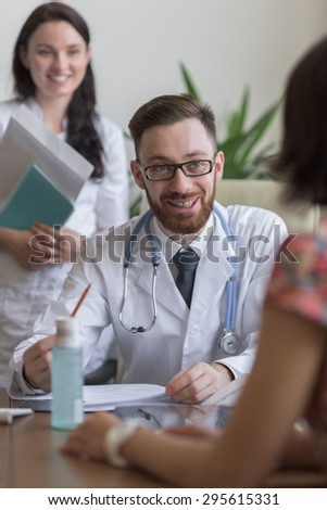 Confident practitioner consulting woman in hospital. Reading test results - stock photo