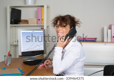 Confident pregnant businesswoman talking on phone while working on laptop at her desk in office