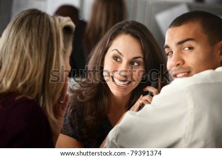 Confident pretty office worker on a phone call as co-workers listen - stock photo