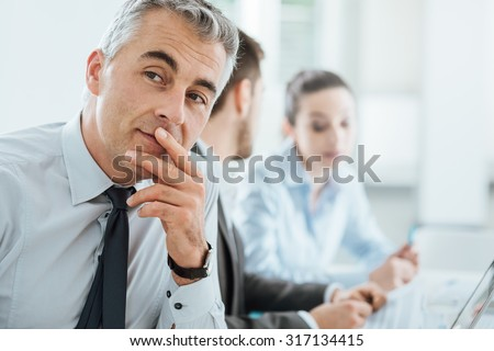 Confident professional business man smiling at camera, office and business team working on background, selective focus - stock photo
