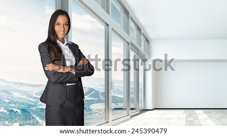 Confident professional female estate agent or broker with a friendly smile in an empty office or apartment with a large open-plan bright white room with panoramic view windows overlooking countryside - stock photo