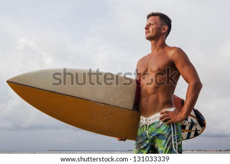 Confident professional surfer with surf board looking at ocean - stock photo