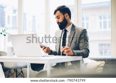 Confident proud ceo with beard reading accounting reports working at digital laptop computer in office building.Male lawyer dressed in formal wear sitting at modern netbook conected to internet