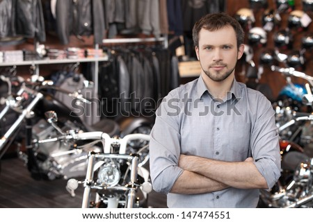 Confident sales executive. Confident young men standing in front of the motorcycles and holding his arms crossed - stock photo