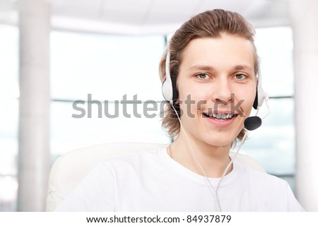 Confident sales representative man with an headset at his workplace. Copyspace - stock photo