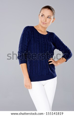 Confident sassy young woman in stylish casual slacks and top standing with her arms folded  studio portrait on grey