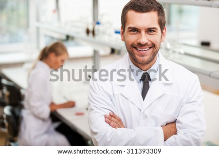 Confident scientist. Happy young male scientist keeping arms crossed and looking at camera while his female colleague working in the background - stock photo