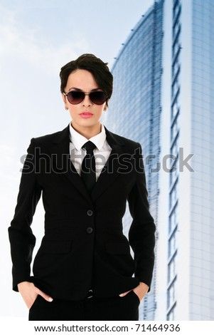 Confident security officer against blue office building - stock photo