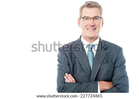 Confident senior business executive with folded arms  - stock photo