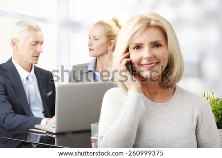 Confident senior business woman making call at office while her colleagues working at background. - stock photo