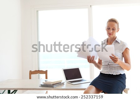 Confident senior business woman sitting on her home office desk handling and reading paperwork, working with a laptop computer, interior. Professional businesswoman using technology. - stock photo