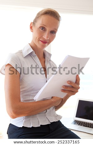 Confident senior business woman sitting on her office desk handling and reading paperwork, working with a laptop computer, smiling indoors. Professional businesswoman using technology at work.