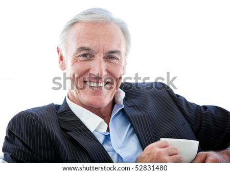 Confident senior businessman drinking a coffee sitting on a sofa - stock photo