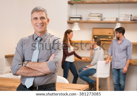 Confident senior businessman keeping arms crossed and standing. Smiling business man with group of business people meeting in office in background. Portrait of a smiling leader looking at camera.   - stock photo