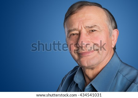 Confident senior male teacher in front of a blank blue background - stock photo