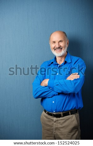 Confident senior male teacher standing with folded arms in front of a blank green blackboard in the classroom - stock photo
