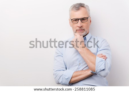 Confident senior man. Confident senior man in formalwear holding hand on chin and looking at camera while standing against white background - stock photo