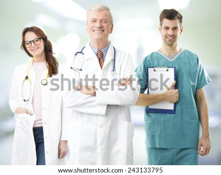 Confident senior professor standing with his team at medical room. - stock photo