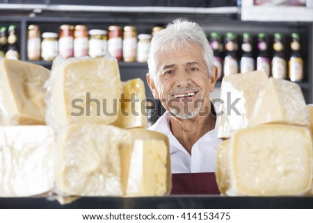 Confident Senior Salesman Smiling In Cheese Shop - stock photo