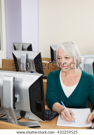 Confident Senior Woman Writing Notes In Computer Class - stock photo