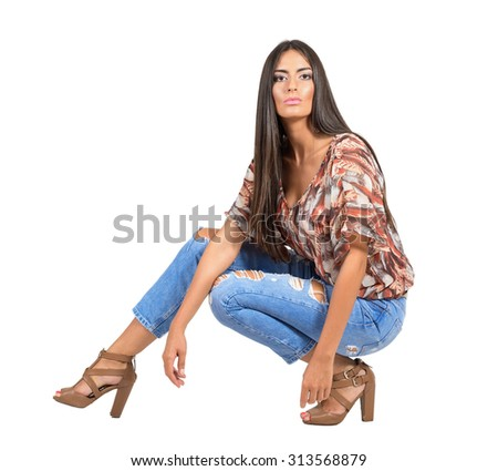 Confident serious young Latin woman in casual clothes crouched pose looking at camera.  Full body length portrait isolated over white studio background.  - stock photo