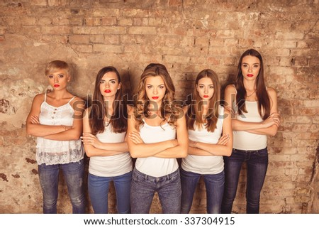 Confident serious young women with red lips wearing dress code