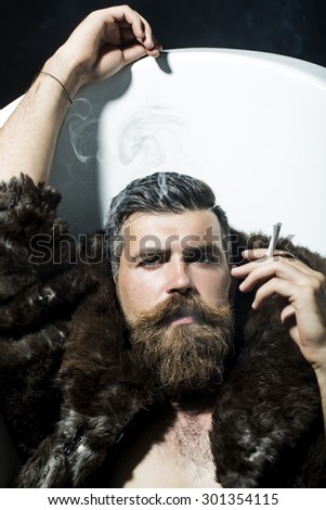 Confident sexy unshaven man with long beard and moustache in brown fur coat with collar and blue jeans lying in white bath tub with raised hand smoking cigarette, vertical picture - stock photo