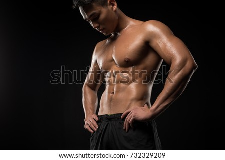 confident shirtless muscular asian man standing with hands on waist and looking down isolated on black