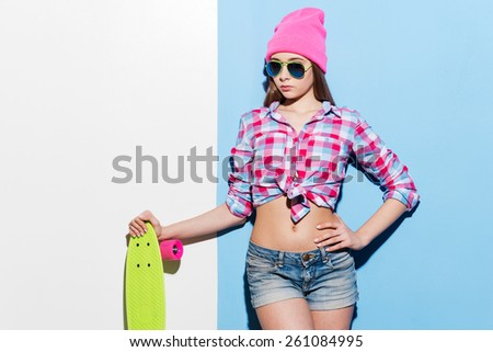 Confident skater girl. Beautiful young woman in pink headwear and sunglasses leaning skateboard while standing against colorful background - stock photo