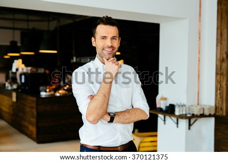 Confident small business owner standing in his coffee shop, restaurant.