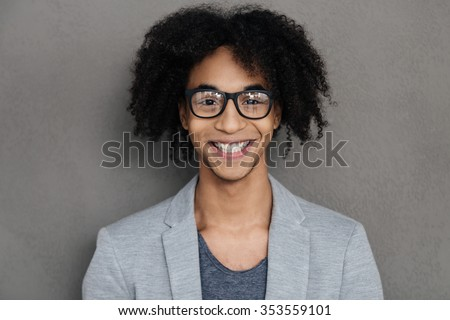 Confident smile. Cheerful young African man looking at camera and smiling while standing against grey background - stock photo