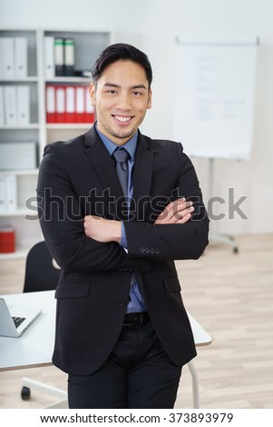Confident smiling Asian businessman standing in the office with folded arms, conceptual of leadership and management - stock photo