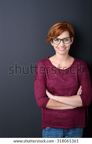 Confident smiling attractive young redhead woman with folded arms wearing glasses standing against a dark studio background with copyspace - stock photo