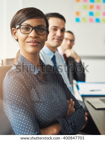 Confident smiling business woman wearing eyeglasses and white polka dotted shirt seated with folded arms beside male co-workers at work - stock photo