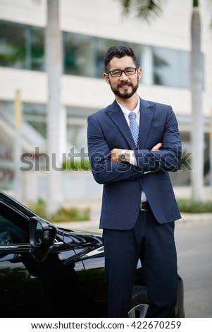Confident smiling businessman standing next to his car