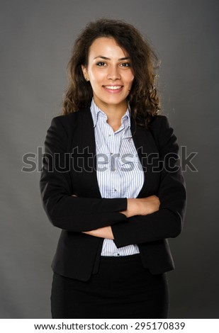 Confident smiling businesswoman with arms folded, on gray background - stock photo