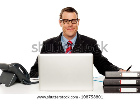 Confident smiling male executive wearing glasses and posing at work desk - stock photo