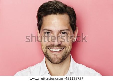 Confident smiling man in pink studio - stock photo