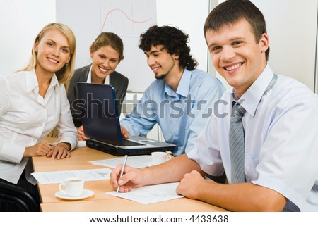 Confident smiling man looking at camera on a background his business team