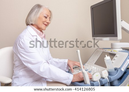 Confident smiling mature female doctor in hospital. - stock photo