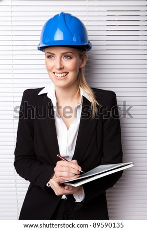 Confident Smiling Woman In Hard Hat holding pen and notebook, upper body - stock photo