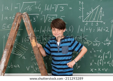 Confident smiling young boy prodigy in school during mathematics class using a stepladder to reach complex equations on the chalkboard - stock photo