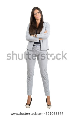 Confident strong business woman with folded arms looking at camera.  Full body length portrait isolated over white studio background.