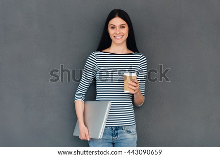 Confident student. Attractive young smiling woman carrying laptop and holding coffee cup while standing against grey background - stock photo