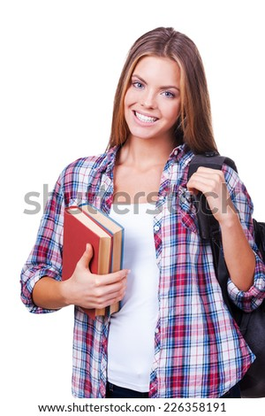 Confident student. Beautiful young women with books carrying backpack and looking at camera