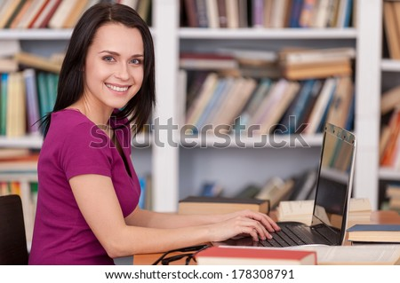 Confident student in library. Side view of cheerful young woman reading a book while sitting at the library desk - stock photo