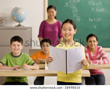 Confident student reads her report in school classroom - stock photo