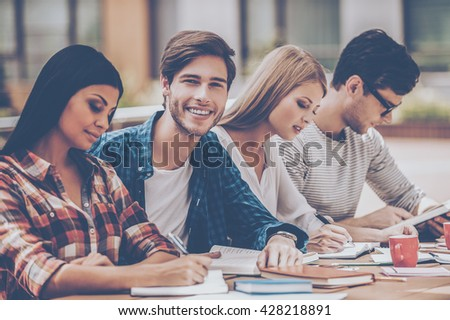Confident students. Joyful young man smiling and looking at camera while sitting with his friends at the wooden desk outdoors - stock photo
