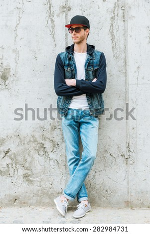 Confident style. Handsome young man in headwear keeping arms crossed while standing against concrete wall  - stock photo