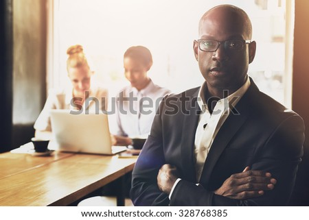 Confident successful black business man in front of group of people - stock photo